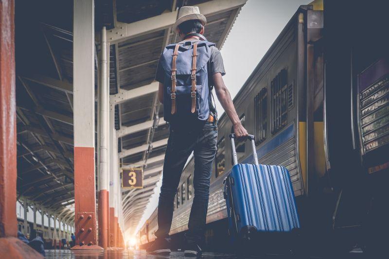 Muž s kufrom a batohom na stanici
