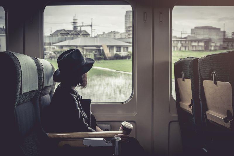 Žena s kávou vo vlaku sleduje výhľad